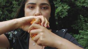 Портрет дерзкого и сексуального брюнета с задавленными tangerines в ее руках девушка выстукивает сок свежих tangerines 4K r видеоматериал