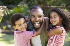 Портрет детей нося отца в саде стоковые фото