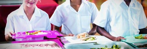 Портрет детей школы имея обед во время периода отдыха стоковые фотографии rf