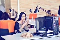 Портрет детенышей пробурил привлекательную женщину на столе офиса, при компьтер-книжка, ища некоторая хорошая музыка Стоковые Фото