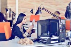 Портрет детенышей пробурил привлекательную женщину на столе офиса, при компьтер-книжка, ища некоторая хорошая музыка Стоковая Фотография
