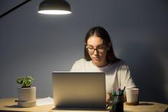 Портрет детенышей утомлял сконцентрированный женский работника офиса на nig Стоковые Изображения