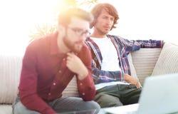 Портрет 2 дизайнеров сети обсуждая проект перед компьтер-книжкой Стоковое Изображение