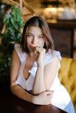 Портрет довольно кавказской коммерсантки сидя на таблице на кресле Стоковое Фото