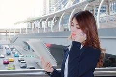 Портрет довольно молодой азиатской секретарши дамы говоря на телефоне и смотря обработку документов в связывателе кольца на город стоковая фотография rf