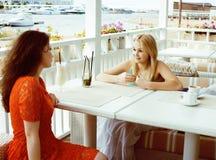 Портрет 2 довольно современных подруг в выпивать кафа под открытым небом внутренний и говорить, имеющ болтовню и coctail стоковые изображения rf