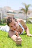 Портрет довольно холодной девушки лежа на траве Стоковая Фотография
