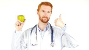 Портрет доктора показывая яблоко с большим пальцем руки вверх, белая предпосылка Стоковые Изображения