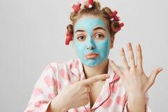 Портрет домохозяйки осадки смешной в pyjamas волос-curlers и голубом лицевом щитке гермошлема указывая на левую руку, спрашивая г стоковая фотография rf