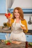 Портрет домохозяйки стоя в кухне держа красочные овощи Стоковые Фотографии RF