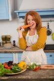 Портрет домохозяйки стоя в кухне, сдерживая моркови Стоковое фото RF