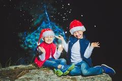 Портрет дружелюбной семьи в Санте покрывает смотреть камеру на вечере рождества Стоковая Фотография RF