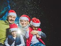 Портрет дружелюбной семьи в Санте покрывает смотреть камеру на вечере рождества Стоковая Фотография