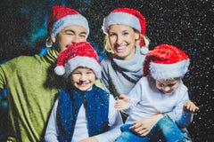 Портрет дружелюбной семьи в Санте покрывает смотреть камеру на вечере рождества Стоковые Изображения