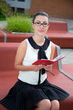 Портрет девочка-подростка в школьной форме сидя на стенде с Стоковое Изображение