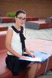 Портрет девочка-подростка сидя на стенде и читая что-то Стоковая Фотография RF