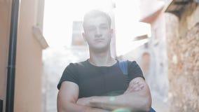 Портрет европейского радостного парня 20s при рюкзак смотря в камеру outdoors в городе Туризм, остатки, образование видеоматериал