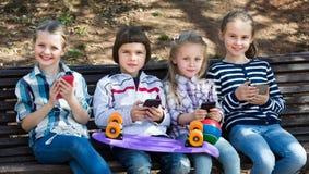 Портрет девушек и мальчиков играя с телефонами Стоковые Изображения RF