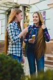 Портрет 2 девушек подростка стоя совместно ел мороженое Стоковые Фото