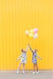 Портрет девушек с воздушными шарами на желтой предпосылке Стоковые Изображения RF