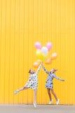 Портрет девушек с воздушными шарами на желтой предпосылке Стоковое Изображение
