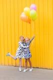 Портрет девушек с воздушными шарами на желтой предпосылке Стоковое Фото