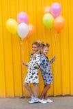 Портрет девушек с воздушными шарами на желтой предпосылке Стоковые Изображения