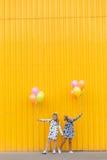 Портрет девушек с воздушными шарами на желтой предпосылке Стоковое фото RF