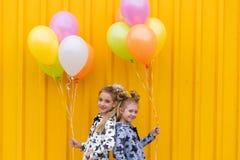 Портрет девушек с воздушными шарами на желтой предпосылке Стоковые Фото