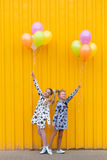 Портрет девушек с воздушными шарами на желтой предпосылке Стоковое Изображение RF