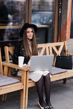 Портрет девушки битника детенышей усмехаясь красивой сидя с портативным портативным компьютером на деревянной скамье на улице Стоковая Фотография