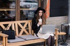 Портрет девушки битника одел в стильных одеждах представляя пока сидящ с сет-книгой на уютном стенде в кафе тротуара Стоковая Фотография
