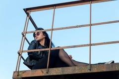 Портрет девушки брюнет, в темных одеждах сидя на balc Стоковое Фото