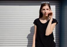 Портрет девушки в стиле черноты утеса, стоя outdoors в городе против стены серебряного металла городской Стоковое Изображение