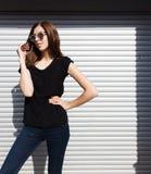 Портрет девушки в стиле черноты утеса, стоя outdoors в городе против стены серебряного металла городской Стоковые Фото