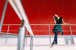 Портрет девушки в стиле черноты утеса, стоя outdoors в городе против красной городской стены Стоковое фото RF
