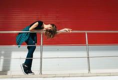 Портрет девушки в стиле черноты утеса, стоя outdoors в городе против красной городской стены Стоковые Изображения RF