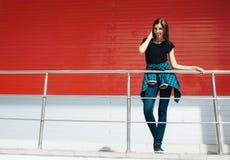 Портрет девушки в стиле черноты утеса, стоя outdoors в городе против красной городской стены Стоковая Фотография