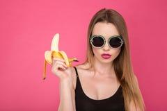 Портрет девушки в черных солнечных очках держа банан Стоковая Фотография RF