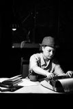 Портрет девушки в шляпе сидя на таблице и печатая на машинке на ноче Стоковая Фотография