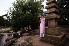 Портрет девушки гейши в нежном розовом кимоно представляя в парке Стоковые Фотографии RF