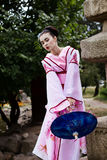 Портрет девушки гейши в нежном розовом кимоно представляя в парке Стоковая Фотография