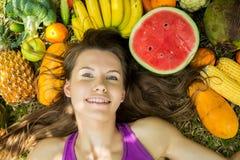 Портрет девушки лежа на траве с фруктами и овощами Стоковые Изображения