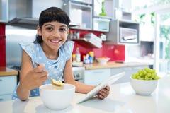 Портрет девушки есть завтрак с цифровой таблеткой в кухне Стоковое Фото