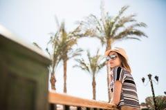 Портрет девушки лета красоты в шляпе и солнечные очки на балконе гостиничного номера смотрят сад ладоней Призвание лета Стоковые Фотографии RF