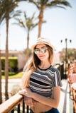 Портрет девушки лета красоты в шляпе и солнечные очки на балконе гостиничного номера смотрят сад ладоней Призвание лета Стоковые Изображения