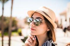 Портрет девушки лета красоты в шляпе и солнечные очки на балконе гостиничного номера смотрят сад ладоней Призвание лета Стоковая Фотография