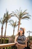 Портрет девушки лета красоты в шляпе и солнечные очки на балконе гостиничного номера смотрят сад ладоней Призвание лета Стоковое Фото