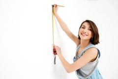 Портрет девушки детенышей усмехаясь милой, измеряя стену с Стоковое Фото