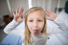 Портрет девушки делая выражение лица в спальне Стоковая Фотография